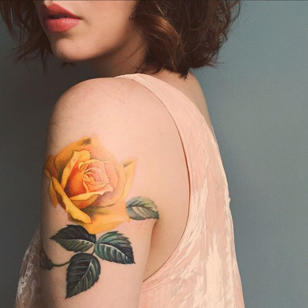Yellow rose tattoo on sleeve