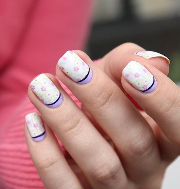 Pretty white and periwinkle spring nail art design. To add to the adorable design are cite little pink roses and leaves to signify the start of spring.