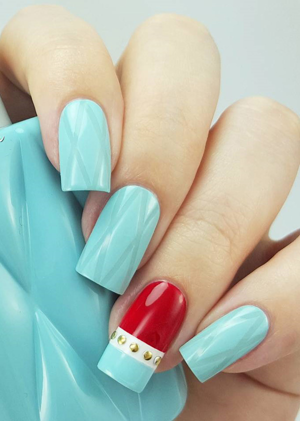 Sea green and bright red spring nail art design. Spring lets you experiment with all the bright colors such as red. This design highlights the bright red polish as well as the gold beads added in between the bottom and tip of the nails.