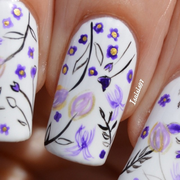 White and violet inspired spring nail art design. Coated with a white base color, simple and cute drawings of violet flowers with black outlines are painted on top giving the nails a cute and homey vibe.