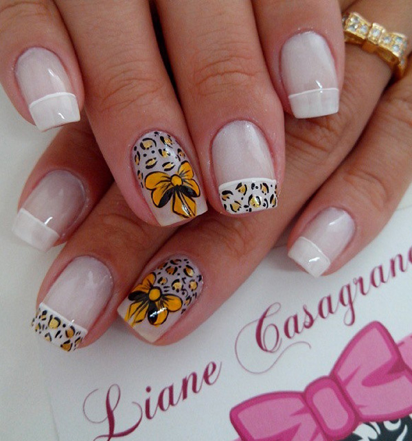 Leopard nail art design in golden rod and white nail polish. The ribbon details for the design look absolutely adorable and goes perfectly with the hand drawn leopard prints around it. The French tips also give the design a uniform and clean appeal.