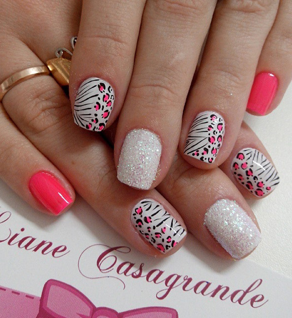 A pretty pink and white leopard nail art design with glitter. Play along with the animal look as the leopard prints are combined with zebra stripes to form this design.