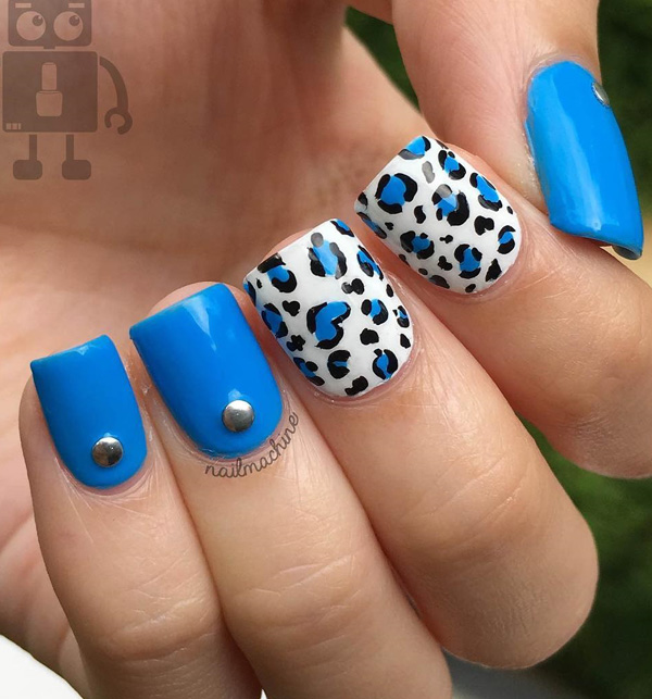 Blue and white leopard nail art design. An electrifying new look for leopard prints as the blue polish completely gives a new kind of life to the design. The silver embellishments on top also make the design look interesting.