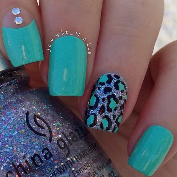 A turquoise blue themed leopard nail art design. The turquoise polish dominates the background of the nail art as well as the leopard prints as it switches to the leopard prints backed by silver dust.