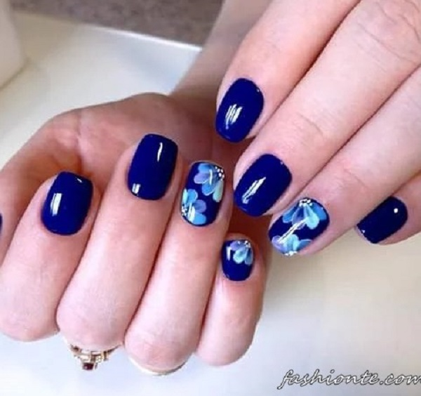 Another flora inspired dark blue nail art design. The blue background is  painted with light - 30 DARK BLUE NAIL ART DESIGNS - Nenuno Creative