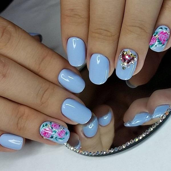 Глянсовий блюз з квітами.  Ще одне натхненне весняне мистецтво нігтів - це наступний наш список.  Спробуйте ці дивовижні глянцеві сині нігті з рожевими квітками, вирізаними, щоб дати йому відчуття дивовижної весни.