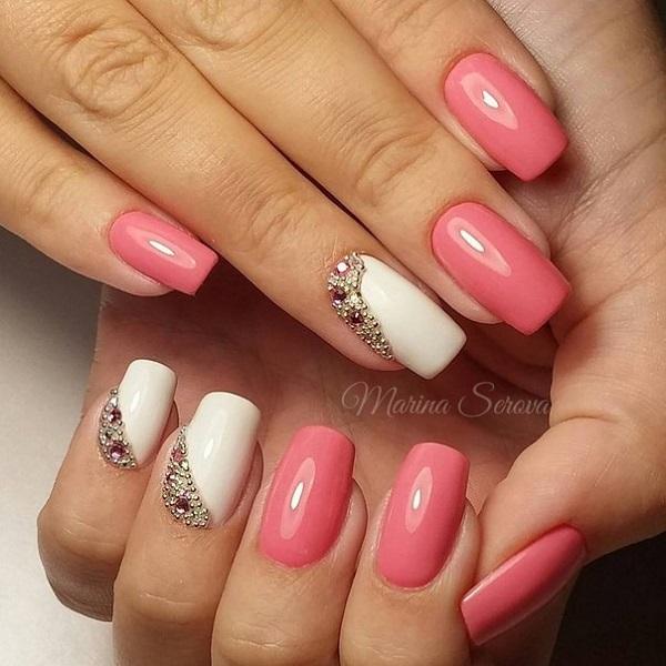 Шиповане весняне мистецтво дизайну нігтів.  Простий, але привабливий, це рожеве і біле нігтівове мистецтво з розташованими діагональними шпильками є ще одним варте спробувати дизайн для весни.