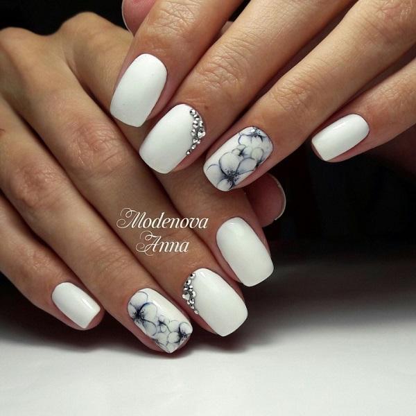 Елегантний дизайн білого дизайну нігтів.  Цей білий анімаційний дизайн нігтів, набитий срібними діамантами і вибитий детальними квітами, є натхненням для весни.