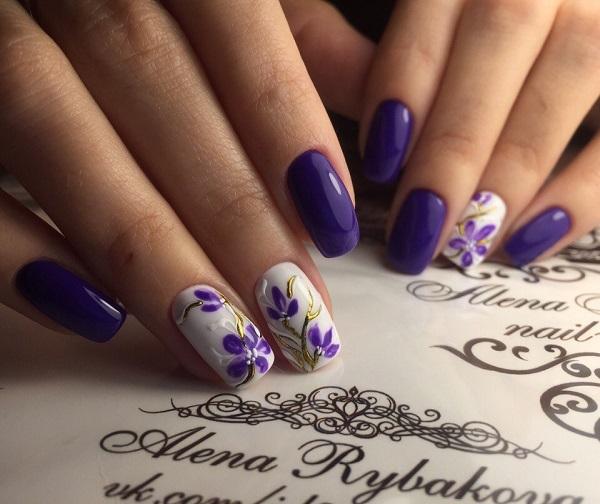 Художній дизайн Nail Art.  Захистіть цвяхи цим дивним синювато-пурпурним і білим дизайнерським дизайном нігтів з висіченими квітами.  Налаштування золота багато чого додає до цього твору мистецтва.
