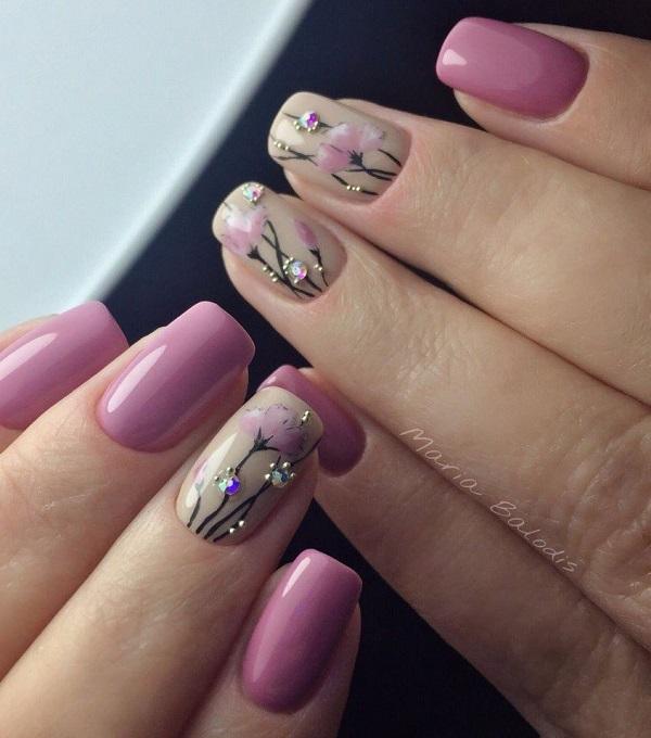 Шипована фіолетова квітка-у дизайні нігтів.  Інший дивовижний дизайн нігтів, який покриває це весняне сезон, - це наступний наш список.  Ця пурпуровая шипована квітка на оголеної основи виглядає неймовірно досконалим, а інші нігті повністю покриті глянсовим фіолетовим кольором.